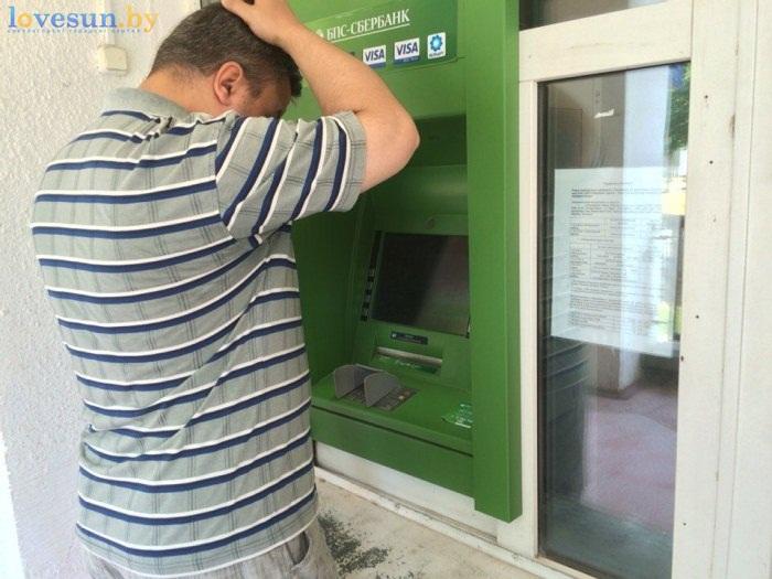 мужчина чешет голову возле банкомата