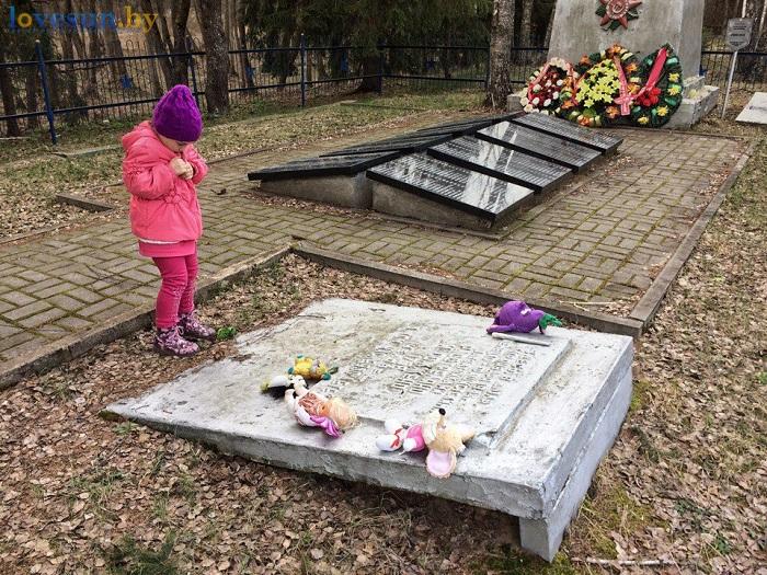 девочка плачет на могиле в сожжённой деревне Ола 04.2017