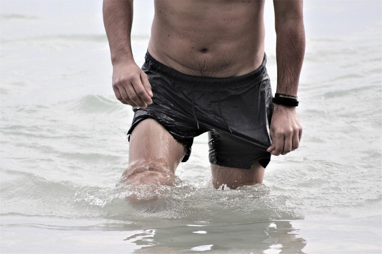Парень в воде в плавках шорты река