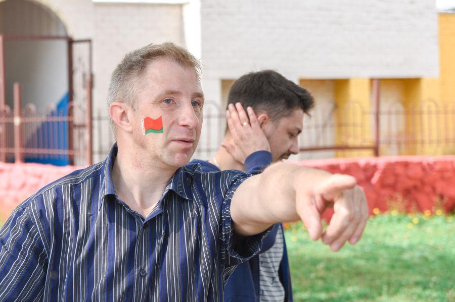мужчина с белорусским флагом показывает пальцем