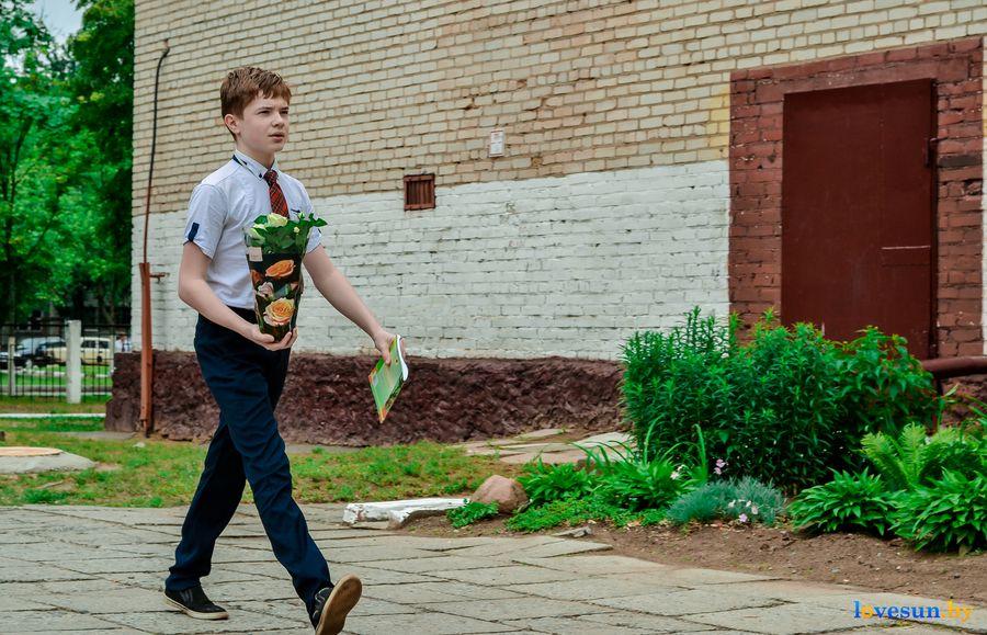 ученик идет с цветами и тетрадкой